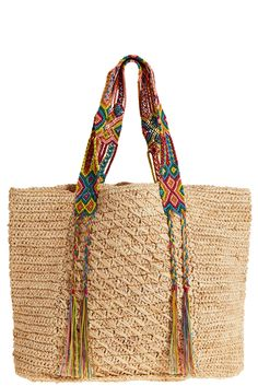 A bohemian take on the classic beach bag, this raffia tote is updated with ethnic inspired accents. Multi colored woven straps on natural raffia provide durable comfort and detail braided tassels for a free-spirited finish. Bag Crochet, Crochet Handbags, My Style Bags, Popular Purses, Boho Bags, Craft Bags, Straw Tote, Knitted Bags, Mode Inspiration