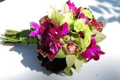 ...bold wrapped bridal bouquet we created using chartreuse and fushia orchids.  We also added a few burgundy dahliahs...to add to the contrast...loved it!