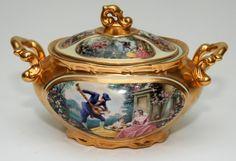 Sopeira em porcelana ricamente decorada com cenas galantes e ornada a ouro. 32 x 18 cm.