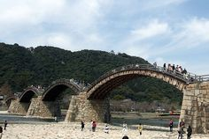 Kintai Bridge a historical wooden arched bridge in the city of Iwakuni, in Yamaguchi Prefecture, Japan.  It was built in 1673, is a series of five wooden arches and spans the Nishiki River.  Declared a National Treasure in 1922, Kikkou Park, which includes the bridge and castle, is one of the most popular tourist destinations in Japan, especially for the Cherry Blossom festival in the spring and the autumn color change of the Japanese Maples.