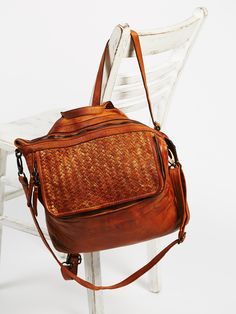 Heirloom Messenger | Made from oh-so soft and buttery leather, this messenger bag features a woven leather pocket with a metallic accent and zipper closure. Zip top with lined interior with slip pockets. Convertible and removable straps transform this messenger into a backpack.