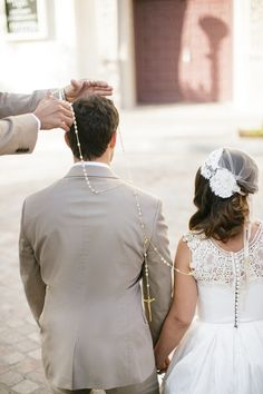 """""""As part of the ceremony to symbolize unity, a large loop of rosary beads is placed in a figure eight shape around the necks of the couple after they have exchanged their vows. The specially appointed 'padrinos' are in charge of lassoing the couple together. The lasso is then gifted to the bride as a souvenir of her taking the groom's hand in marriage & symbolizes their commitment to each other."""""""