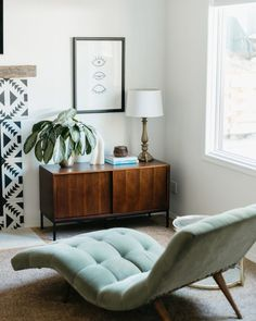 A light green chaise plays off the midcentury sideboard and modern graphic tile for an eclectic mix of eras!