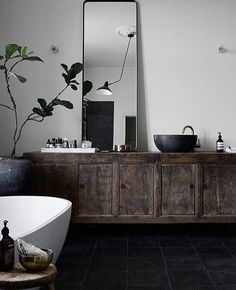 vintage old cabinet has been repurposed as a vanity. vessel stone sink and mid century black cone lamp gives a european spa feel to this bathroom