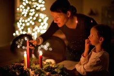 Preparing for Christmas With the Advent Wreath: A mother and daughter light an Advent wreath.