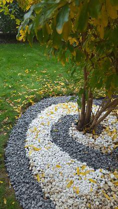 spirale con sassi di marmo neri e bianchi attorno al melograno in giardino (con foglie autunnali già cadute!)