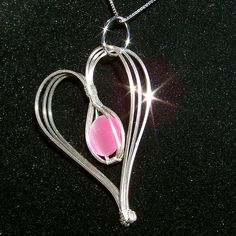 Pink Cat's Eye Heart Pendant by innerdiameter. No tut but I plan to figure it out.  The cage in the center is ingenious, and I think the designer's use of square wire enhances the lines of the design.