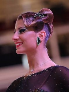 High bun with bang swoop and small rhinestoned accessory. Good hairstyle for standard and latin. Visit http://ballroomguide.com/comp/hair_make_up.html for more hair and makeup info