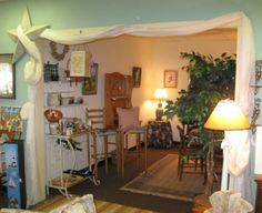 """Using yardage and a big, 3D wall ornament like this star, a consignment shop makes a """"spare room"""" into a true showcase. TGtbT.com suggests that such simple & inexpensive touches increase the perceived value of your merchandise."""