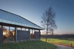 Golf clubhouse: zinc coated roof, wooden window frames, brick wall. Golf clubhuis: zinken dakbekleding, houten kozijnen, gemetselde bakstenen gevel.