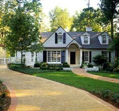 charming traditional house exterior with black shutters, looks like grey painted brick. Very nice curb appeal with curved driveway.