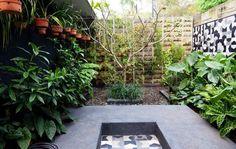 arrière-cour avec pots suspendus et mur végétal fait de lits en bois