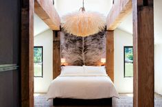 Designed by Erin Martin  Don't be afraid to break design rules. The bedroom's high ceilings and rustic beams make for a restful room.