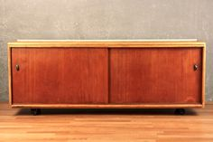 Retro danish modern sliding-door credenza with a raw wood top and a Teak front. Offers plenty of storage. In overall good condition with some minor wear. Dimensions: 63.5 w 18 d 24 h