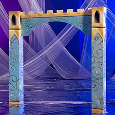 The Fairytale Castle Arch has an elegant design of gold swirls adorning a light blue column and top.