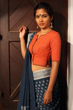 Thumbapoo Blouse ~ Manjal – Seamstress This blouse is our take on the iconic shirt blouse worn by fiery women writers and freedom fighters of Kerala. Classic and elegant like the women who wore them. The tiny coloured embroidery motifs on the saffron blouse are reminiscent of the thumbapoo flower and add to its simple allure.