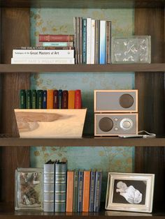 Bookcase Arranging Basics  The bookcases are decorative and functional. Stacking books both horizontally and vertically, as well as filling bins with books, creates an interesting display. There is also space for a small radio and MP3 player, which provide background music for dinner parties or reading time.    Get the Look: Personalize your bookshelves by using framed photographs as bookends. Don't worry about matching frames because the photos will grab guests' attention.