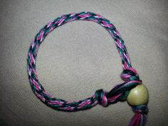 kumihimo style bracelet, using 16 strand design and 4 colors (pink, purple, teal, and black)
