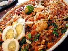 Singapore Street Food - Mee Siam is a dish mainly offered by Malay hawkers. It comprises of bee hoon or vermicelli and a spicy tangy gravy topped with boiled eggs, shallots, fried tofu and other garnishing.