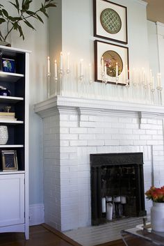 White fireplace & walls with lovely glass candlesticks.