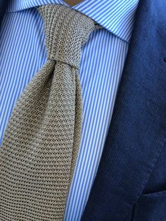 Navy jacket, white shirt with blue dress stripes, beige knit tie
