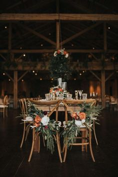 The Design Eye Candy Doesnt Quit in This Devils Thumb Ranch Wedding These rustic wooden chairs are decorated with lush greens orange flowers Wedding Table Centerpieces, Wedding Flower Arrangements, Flower Centerpieces, Diy Wedding Decorations, Centerpiece Ideas, Flowers Decoration, Rustic Wedding Tables, Wedding Favors, Fall Wedding Table Decor