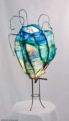 Seed Pod - Mixed media sculpture - layers of reed, tissue paper, wire and image transfers illuminated by an internal light bulb