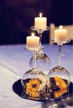Copas volteadas con flor y vela a diferentes alturas