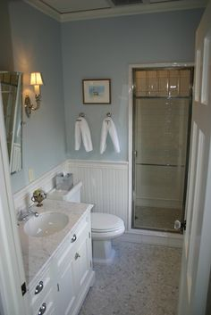 Chic cottage beachy bathroom design with blue walls paint color, chair rail with beadboard, white bathroom cabinet, calcutta marble counter top, rectangular pivot mirror, and white carrara marble hexagon hex tiles floor.