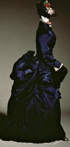 Walking dress, ca. 1884. Navy silk satin and silk faille moiré. Overskirt of silk satin draped toward back & connected to large bustle. Skirt trim of pleated silk faille moiré. Kyoto Costume Institute