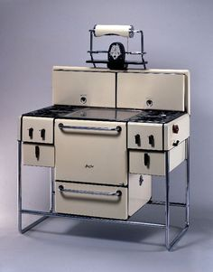 1935 Magic Chef Yellow and black enameled metal stove with lidded burners and two drawers on either side of central oven and drawer underneath for pots and pans; sits on chromed metal tubular legs.