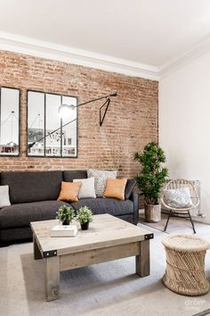 Salón con pared de ladrillo visto, sofás y espejos