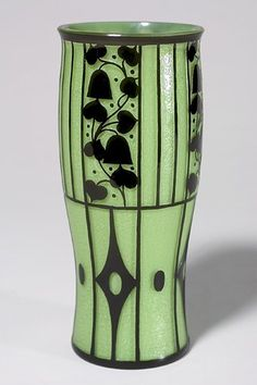 "Loetz vase by Josef Hoffmann, ca.1911. This design represents some of Hoffmann's most important workmanship: Cylindrical form done in apple green overlaid with an opaque ebony design. The top portion is etched in silhouette of climbing vines, bearing bell flowers, berries and leaves, set apart by vertical bars. The lower portion has an arrangement of diamond configurations that alternate with elliptical forms. H: 10 1/8"" Wiener Werkstatte"