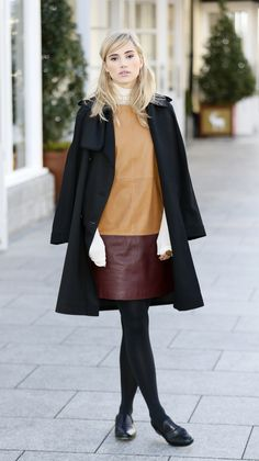 Suki Waterhouse leather skirt black coat sweater tights street style. Love her bangs.