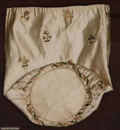 """""""Augusta Auctions closeup of embroidery on silk reticule""""  """"18th C white silk satin, paper stiffened round base, polychrome sprig embroidery & tambour stitch leaf wreath around base, Ht 9.5"""", Wd 9.25"""","""