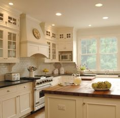 cream cabinets with white subway tile, dark countertop and wood countertop island
