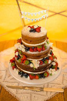 Tiered Victoria sponge wedding cake with mini bunting cake topper – photography http://www.bohemianweddings.co.uk/
