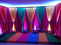Colorful Mehndi backdrop with long seat pillows make a beautiful and festive statement for any Indian event or pre-wedding ceremony. Draping by Chair Divas.