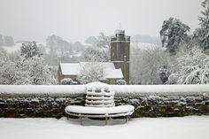 winter snowy view of huntsham village church from huntsham court forecourt terrace.