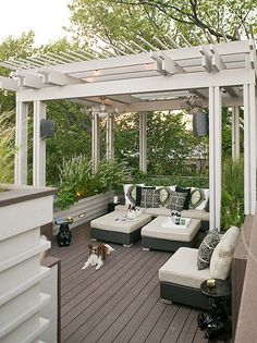 White pergola over a stained deck and classic all-weather outdoor chairs and chaises.