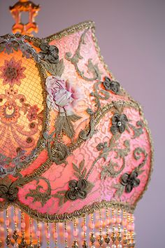 Hand-painted antique table lamp holds a hand-dyed French Rosette Cameo silk lampshade with shadowbox. Shade is dyed ballet pink to light rose covered with antique textiles in tones of cream, pink and gold. These antique fabrics include circa 1918 ribbon rosettes from France and gold metallic laces and scroll work. The shadowbox contains a pretty Edwardian era appliqué with netting, overlaid with net and small floral appliqués. Hand-beaded fringe in golds, pale pinks, greens and pearl.