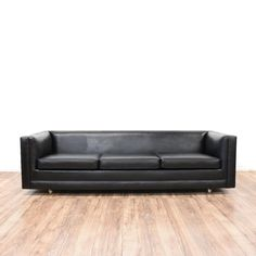This mid century modern sofa is upholstered in a durable vinyl with a shiny black finish. This sleek sofa has a low back with straight arms and a rolling caster wheel base. Stunning and timeless couch perfect for a modern living room! #midcenturymodern #sofas #sofaorcouch #sandiegovintage #vintagefurniture