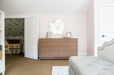 Gorgeous pink girl's bedroom features a Made Goods Fiona Mirror mounted to a wall painted Benjamin Moore Melted Ice Cream above a Bungalow 5 Ming Extra Large 8 Drawer Brown Dresser positioned under a vaulted ceiling.
