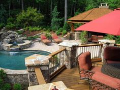 Multiple play areas and plenty of lounging options coexist happily in this beautiful hardscape, perfect for relaxing and entertaining. Rock columns on the deck perimeter help unify the look.