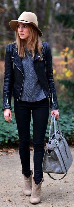 Look com blusa cinza e jaqueta de couro com calça preta e botas com bolsa e chapéu como acessórios