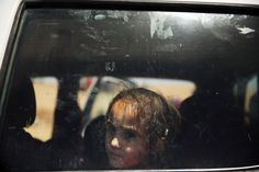 Jul. 1, 2014. An Iraqi girl look out of a window as over 1000 Iraqis who have fled fighting in and around the city of Mosul and Tal Afar wait at a Kurdish checkpoint in the hopes of entering a temporary displacement camp in Khazair, Iraq.