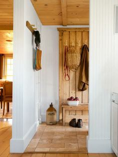 In keeping with this home's farmhouse heritage, the mudroom is simply decked out with ample hanging space on beadboard walls and a hardworking limestone floor. | Photo: John Gruen | thisoldhouse.com