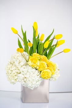 Centerpieces Yellow roses hydrangeas tulips Modern contemporary silver vase
