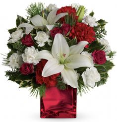 Filled with holiday charm. Red spray roses and white asiatic lilies are arranged to perfection in our beautiful glass cube.