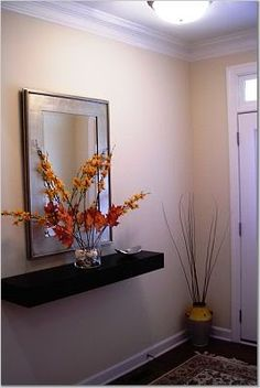 Staging idea for a blank non inviting entry. Add a Floating shelf and Mirror